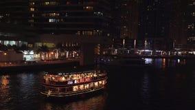 Giro di notte su un yacht tramite un canale nel video costoso del metraggio delle azione del porticciolo del Dubai di zona turist stock footage