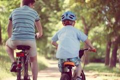 Giro felice del figlio e del padre sulle bici Fotografie Stock Libere da Diritti