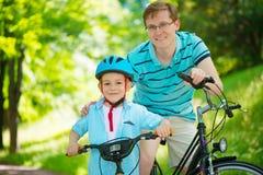 Giro felice del figlio e del padre sulle bici Fotografia Stock Libera da Diritti