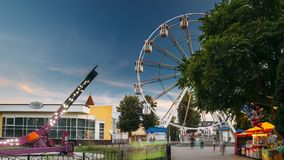 Giro na atração iluminada Ferris Wheel On Summer Evening do movimento efeito natural no parque de diversões da cidade video estoque