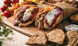 Girocompases griegos envueltos en panes Pita en una tabla de madera Imagen de archivo libre de regalías
