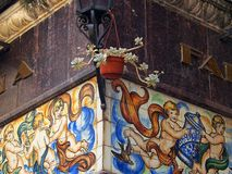Tiled Building Detail, Girona, Spain. Flower pot and tiled mosaic with religious, allegorical, motifs, street corner, Girona Old Town, Spain Royalty Free Stock Image
