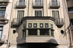 Girona, Spain, August 2016. A fragment of an interesting old building with stained glass on the balcony. The dwelling house in Art Nouveau style built in the royalty free stock photography
