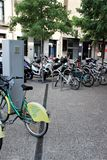 Girona, Spain, August 2018. Parking of bicycles and motorcycles in the city center. Pavement, paved with gray granite slabs, rental of city bicycles, mopeds in royalty free stock photography