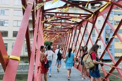 Girona, Spain, August 2018. Tourists on the famous red iron bridge. Young men and women are photographed with pleasure on a pedestrian bridge in the old town stock images