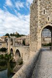 View along romanesque bridge over the Fluvia river, arches and defence towers showing royalty free stock photo