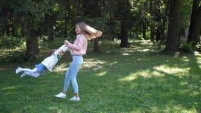Giros jovenes de la madre con el niño en el parque del otoño Juego y risa felices con la hija Cámara lenta 4K almacen de metraje de vídeo