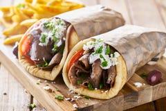 Giroscópios gregos da carne do cordeiro com molho do tzatziki, queijo de feta e batatas fritas imagem de stock