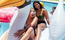 Girs ayant l'amusement sur un jouet gonflable dans la piscine Image libre de droits