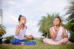 Girs-Spiel und genießen Tätigkeiten Schlagblasen im Park, Freundschaft an Kind-` s Tag stockbild