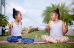 Girs-Spiel und genießen Tätigkeiten Schlagblasen im Park, Freundschaft an Kind-` s Tag stockfotos