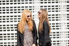 Girsl de dos jóvenes que cuelga hacia fuera en la ciudad Foto de archivo libre de regalías