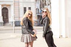 Girsl de dos jóvenes que cuelga hacia fuera en la ciudad Imagen de archivo libre de regalías