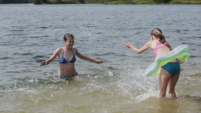 Girsl splashing in the lake. Young girls play in the water, splashing into each other.Family vacations on the lake, river.Summer vacation stock footage