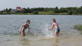 Girsl splashing in the lake. Young girls play in the water, splashing into each other.Family vacations on the lake, river.Summer vacation stock video