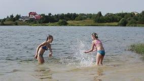 Girsl splashing in the lake stock video