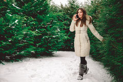 Girtl in forest walking and talking on the phone. Girtl in snowy green forest walking and talking on the phone Royalty Free Stock Images