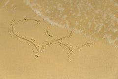 Gischt wäscht das Kennzeichen von Herzen auf dem Sand Lizenzfreie Stockbilder