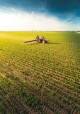 Gisement de pulvérisation de soja de tracteur au ressort photographie stock