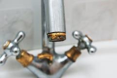 Gisement et rouille d'eau calcareuse sur le robinet dans la salle de bains images stock