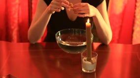 Gissa med en stearinljus hällande vax för kvinna in i vattnet Kvinnliga händer tar det kylde vaxet ut ur vattnet Undersökande a arkivfilmer