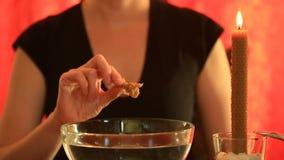 Gissa med en stearinljus hällande vax för kvinna in i vattnet Kvinnliga händer tar det kylde vaxet ut ur vattnet Undersökande a lager videofilmer