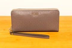 Gissings est 1981 portefeuille op houten lijst De gissing is een Amerikaanse kledingsmerk en een detailhandelaar royalty-vrije stock fotografie