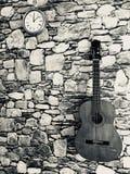 Gitaar en klok de muziekachtergrond van de muursteen Royalty-vrije Stock Foto's