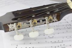 Gitaar hoofdclose-up op muzieknota's Stock Foto