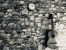 gitaar, klok, zwart-witte steenmuur Royalty-vrije Stock Afbeelding