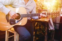 Gitaar met man mannelijke handen die de gitaar op houten muurgitaar als achtergrond, elektrische of akoestische met aardlicht spe stock foto