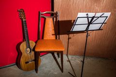 Gitaar, stoel en lessenaar in een laag milieu dat van de begrotingsstudio wordt getoond royalty-vrije stock fotografie