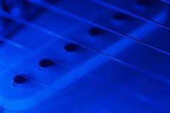 Gitaarbestelwagen en koorden in blauw licht Royalty-vrije Stock Foto's