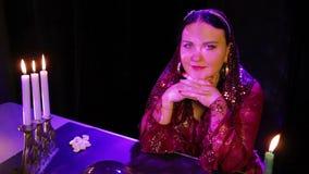 Gitan songeur dans une table magique par lueur d'une bougie banque de vidéos