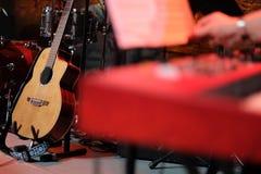 Gitara akustyczna na scenie wśród instrumentów muzycznych Zdjęcia Royalty Free