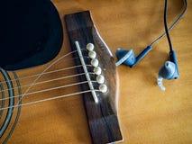 Gitara akustyczna z łamanymi gitara sznurkami, słuchawką i Obrazy Royalty Free