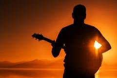 Gitara Bawić się przy zmierzchem zdjęcie royalty free