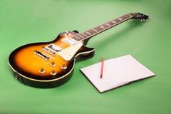 Gitara elektryczna z notatnikiem na zielonym tle fotografia royalty free