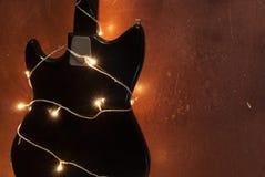 Gitara elektryczna z zaświecającą girlandą na brown grunge tle Zdjęcie Stock