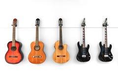 5 gitaren die voor een witte muur hangen royalty-vrije stock fotografie