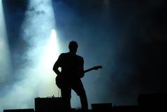 Gitarist bij overleg wordt gesilhouetteerd dat Stock Foto's
