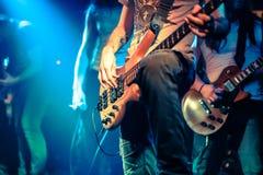 Gitarist die elektrobasgitaar op een rotsjol spelen Stock Foto