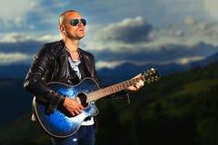 Gitarist met blauwe akoestische gitaarspelen in aard royalty-vrije stock fotografie