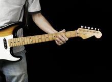 Gitarist met elektrogitaar in zwarte Stock Foto's