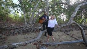 Gitaristspelen voor blonde meisjeszitting op tak bij bomen stock videobeelden