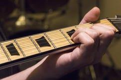 Gitarrövning under det dunkla ljuset royaltyfri foto