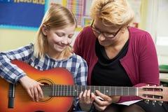 Gitarr för lärareHelping Pupil To lek i musikkurs Fotografering för Bildbyråer