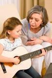 Gitarr för ung flickaallsångspelrum till farmodern arkivfoto