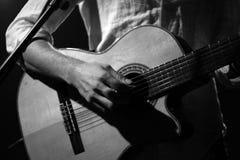 Gitarr grabb, spela som är svartvitt, konsert arkivfoto