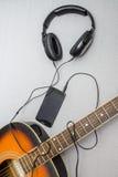 Gitarr, hörlurar, kontur av en gitarrist som spelar och mobiltelefon royaltyfri fotografi